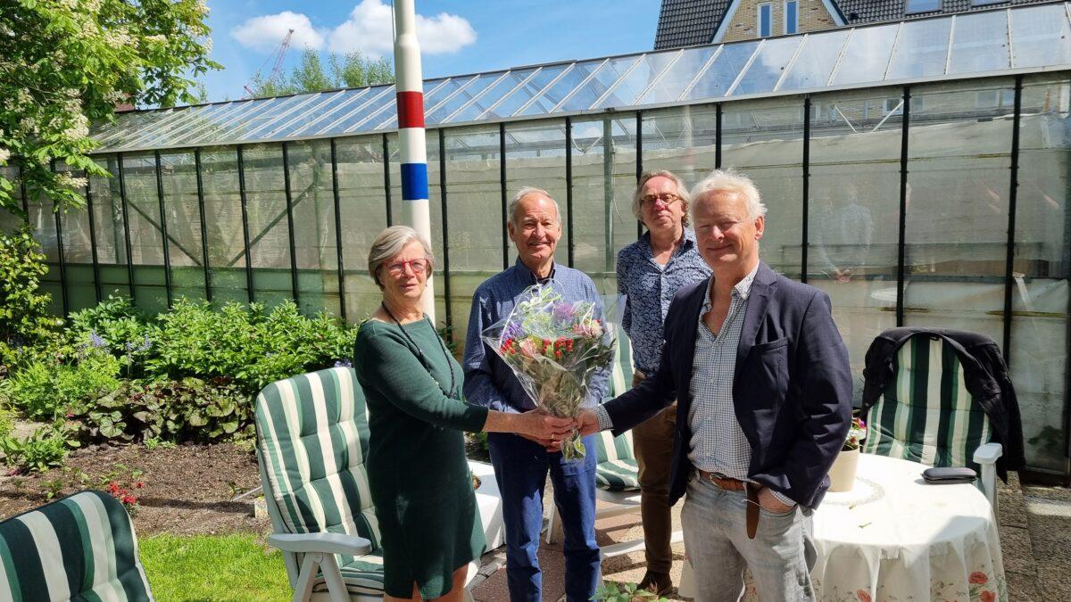 Voorzitter Lucas van Wees overhandigt Aad en Toni van der Meer de bloemen. Op de achtergrond Jan van der Mast.